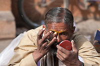 Pashupatinath, Nepal.  Sadhu (Holy Man) at Nepal's Holiest Hindu Temple Looking in Mirror as he Prepares to Decorate his Face.