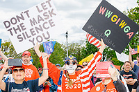 """A woman wears Trump 2020 campaign shirt, hat, and earrings, and a facemask reading """"Tastes like socialism"""" while holding signs reading """"Don't let the mask silence you"""" and """"WWG1WGA / Q / #Obamagate"""" as people gather for an anti-lockdown protest organized by the alt-right group Super Happy Fun America near the home of Massachusetts governor Charlie Baker in Swampscott, Massachusetts, on Sat., May 16, 2020. The black sign contains references to the QAnon conspiracy  theories (""""Where we go one, we go all"""")prevalent among fringe conservative circles. """"Obamagate"""" has recently been talked about by US President Donald Trump without reference to what the """"Obamagate"""" scandal might be. The other side of the sign reads """"Is this about the virus or the election."""" The protest was in defiance of Massachusetts orders mandating face coverings and social distancing and prohibiting gatherings larger than 10 people during the ongoing Coronavirus (COVID-19) global pandemic. The state's stay-at-home order is expected to be updated on May 18, 2020, with a phased reopening plan issued by the governor as COVID-19 cases continue to decrease. Anti-lockdown protests such as this have become a conservative cause and have been celebrated by US president Donald Trump. Many of the protestors displayed pro-Trump messages or wore Trump campaign hats and shirts with phrases including """"Trump 2020"""" and """"Keep America Great."""" Super Happy Fun America, organizers of the protest, are an alt-right organization best known for creating the 2019 Boston Straight Pride Parade."""