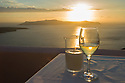 Santorini, Greece. 09.05.2012. Table with candle and glass of Assyrtiko white wine, overlooking the Caldera, at sunset in Fira, Santorini. Photograph © Jane Hobson.