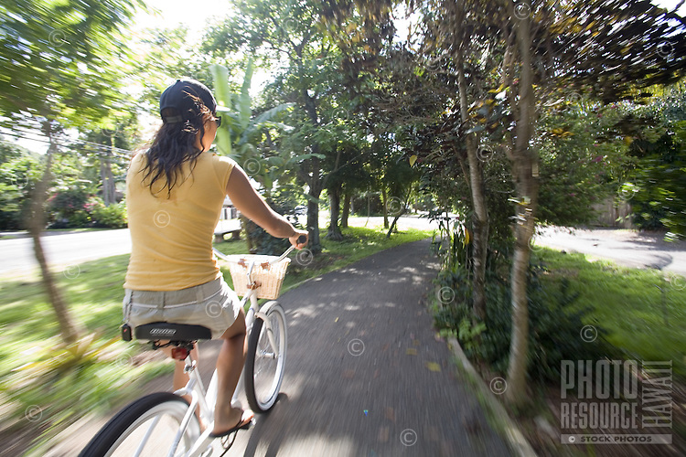 Young woman riding a cruiser bike through trees on the scenic North Shore bike path