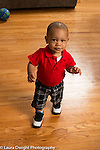 12 month old baby boy walking in living room at home