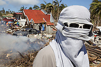 Philippines. Province Eastern Samar. Hernani. 95 % of the town was destroyed by typhoon Haiyan's winds and storm surge. A man with sunglasses covers his face and head with a polo shirt. He protects himself from sun's heat and smokes of burning waste. Typhoon Haiyan, known as Typhoon Yolanda in the Philippines, was an exceptionally powerful tropical cyclone that devastated the Philippines. Haiyan is also the strongest storm recorded at landfall in terms of wind speed. Typhoon Haiyan's casualties and destructions occured during a powerful storm surge, an offshore rise of water associated with a low pressure weather system. Storm surges are caused primarily by high winds pushing on the ocean's surface. The wind causes the water to pile up higher than the ordinary sea level. 25.11.13 © 2013 Didier Ruef