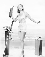Woman in a bathing suit at the beach holding an oversized fire cracker in her hands