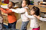 Education preschool 4 year olds music activity group of children singing in a line hands on each other's shoulders horizontal