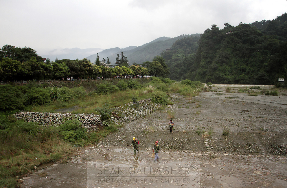 """Workers walk up one of the channels that make up the Dujiangyan Irrigation System. The system is regarded as an """"ancient Chinese engineering marvel."""" By naturally channeling water from the Min River during times of flood, the irrigation system served to protect the local area from flooding and provide water to the Chengdu basin. Sichuan Province. 2010"""
