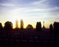 The sun sets behind headstones and The Cross of Sacrifice at Tyne Cot, the biggest Commonwealth War Cemetery in the world where almost 12,000 men, killed in the Ypres Salient during World War I, are laid to rest.