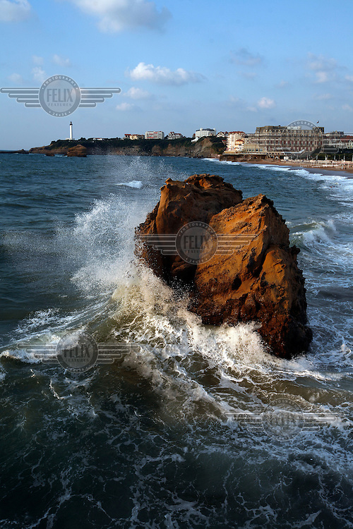 Characteristic rocks at in the sea by the Grande Plage beach with the famous Hôtel du Palais in the background. Biarritz,France.