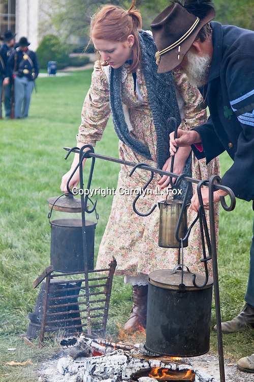 A woman helps at the camp of union soldiers during a Civil War reenactment.