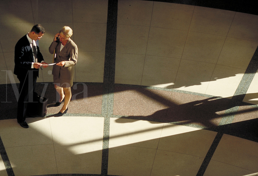 Man and woman discussing business; on cell phone; looking over documents. High view. Professionals. Lawyers. Businesswoman. Businessman. Denver Colorado USA.