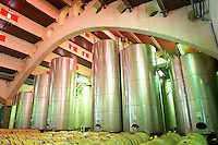 Wine aging in oak barrels. Modernista style vaulted winery. Oak barrel aging and fermentation cellar. Fermentation tanks. Raimat Costers del Segre Catalonia Spain