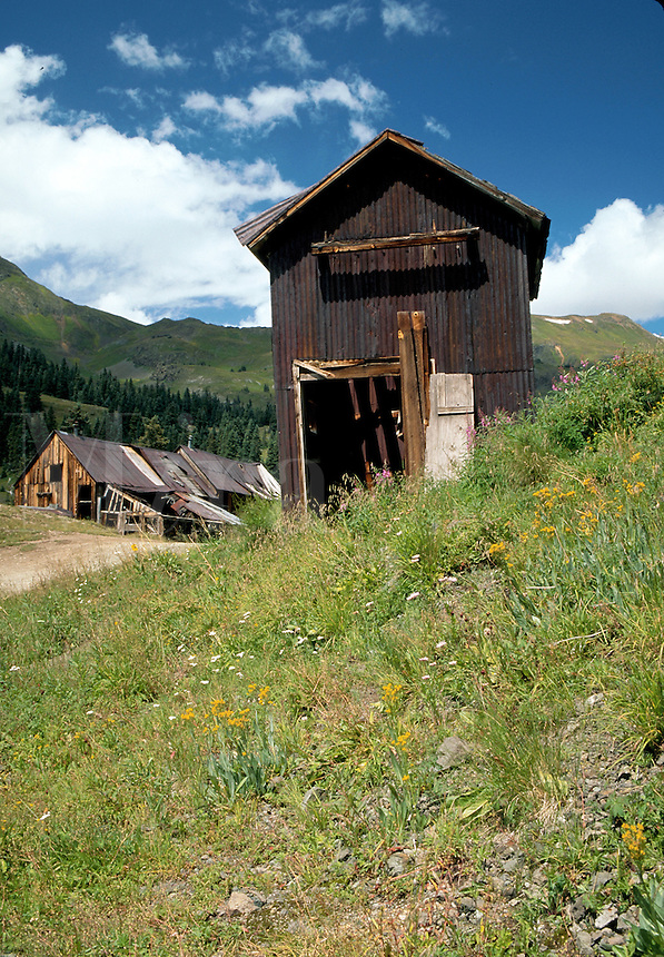 Old wood frame mine shacks provide a rusticcontrast to the backdrop of rolling green hills. Rocky Mountains, Colorado.
