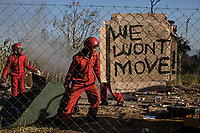 """The Red Ants evict a small community from a disputed piece of land in Capital Park, Pretoria. Some members of the community claim to have lived there for 30 years. A white-owned consortium who claim to be the rightful owners of the land obtained a court order to evict the community. The community has been offered alternative housing in a """"container"""" village on the outskirts of the city. <br />The Red Ants are a controversial private security company often hired to clear squatters from land and so-called 'hijacked' properties."""