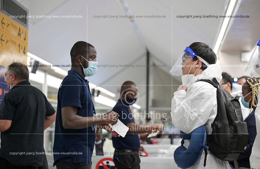 IVORY COAST, Abidjan, airport, chinese traveller with protection wear during Corona Pandemic time at gate on flight to Paris, passport check / ELFENBEINKÜSTE, Abidjan, Flughafen, Chinesische Reisende in Schutzkleidung während der Corona Pandemie