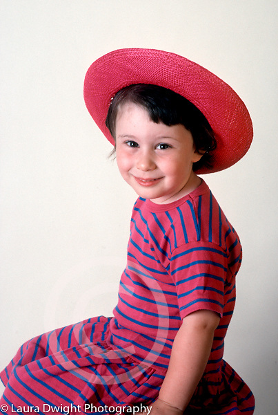 3 year old girl sitting on stool closeup portrait wearing hat Caucasian vertical