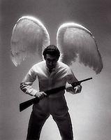 Man wearing angel wings holding shotgun<br />