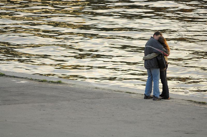 Poland, Krakow, Couple embracing beside River