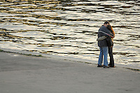 Poland, Krakow, Couple embracing beside River