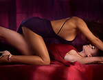 Romantic sensual photo of a sexy lesbian couple making love on a bed, two beautiful women in blue and red dresses, one on top of another about to kiss Image © MaximImages, License at https://www.maximimages.com