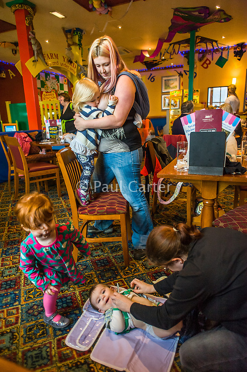 A mother breastfeeds her two year old daughter with her twelve week old baby asleep in a sling on her back.in the family restaurant and play area of a pub. The mother is standing and the boy is feeding while standing on a chair. In the foreground another mother is changing a nappy.<br /> <br /> Lancashire, England, UK<br /> <br /> Date Taken:<br /> 07-01-2015<br /> <br /> © Paul Carter / wdiip.co.uk