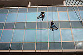 Two men clean the windows of an office building in Camden Town, London, using ropes and harnesses.