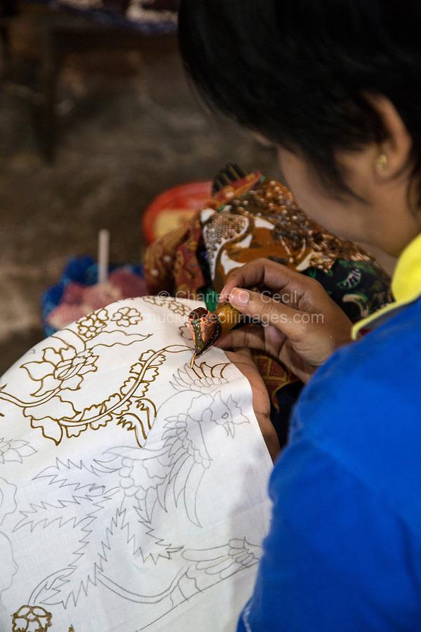 Yogyakarta, Java, Indonesia.  Batik Workshop.  Female Worker Applying Wax to Batik Design.