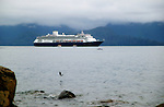 A salmon leaps out of the water while the Holland America cruise ship, Amsterdam, off loads passengers in Sitka Bay, Alaska.