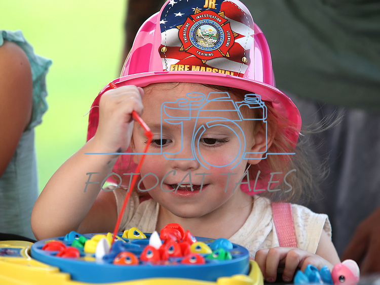 Roulette Nicole Patellos, 2, plays a fishing game at the DARE booth at the 16th annual National Night Out event, hosted by the Carson City Sheriff's Office, in Carson City, Nev., on Tuesday, Aug. 7, 2018.<br />Photo by Cathleen Allison/Nevada Momentum