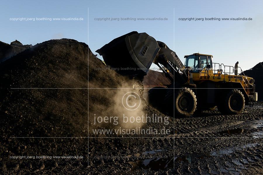Germany, Hamburg, Hansaport import of coal and ore for steel plants and coal power stations, coal storage place in contrast with wind turbine in harbour / DEUTSCHLAND, Hamburg, Hansaport, Import von Kohle und Erz, Lagerung und Weitertransport zu Kraftwerken und Stahlwerken