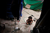 A child plays with a hoop as the Jhon Danyer circus is packed up to move on. After two to three weeks in a neighbourhood the circuses move on as they have exhausted their market. There are ever fewer spaces to perform as the city grows and develops. Around a dozen small circuses wander the poorer neighbourhoods around the city of Medellin putting on performances in what can be a hand to mouth existence. Despite falling audience numbers, new health and safety regulations and other bureaucracy these small family businesses, many of whom have existed for generations, still scrape a living in a world where the people are more accustomed to being entertained by soap operas than by live entertainment.