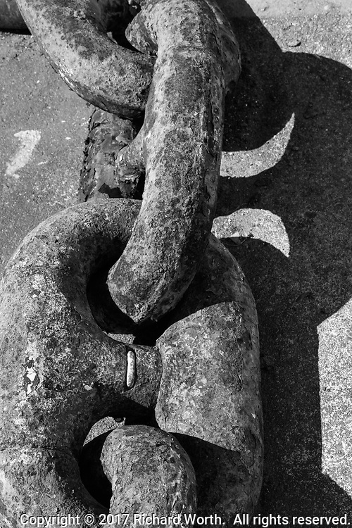 Two huge, rusted links in an anchor chain on the dock next to the USS Hornet Museum.