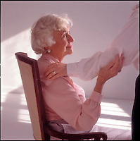 Seated older woman toching arm of younger woman