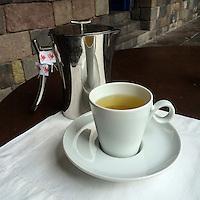 Peru.  Peruvian Cuisine.  Coca Tea, Said to Lessen the Symptoms of Altitude Sickness at Cusco's 11,000-foot Altitude.  Inca Stonework in Background.
