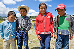Three boys and a girl pose near a church in San Nicolas, Western Highlands, Guatemala
