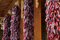 Red peppers drying on posts under eave of New Mexico house