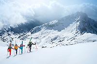 A ski tour through the Pirin Mountains of Bulgaria. Skiers carry their skis on the Kamenitsa Mountain from the Tevno Ezero Hut.