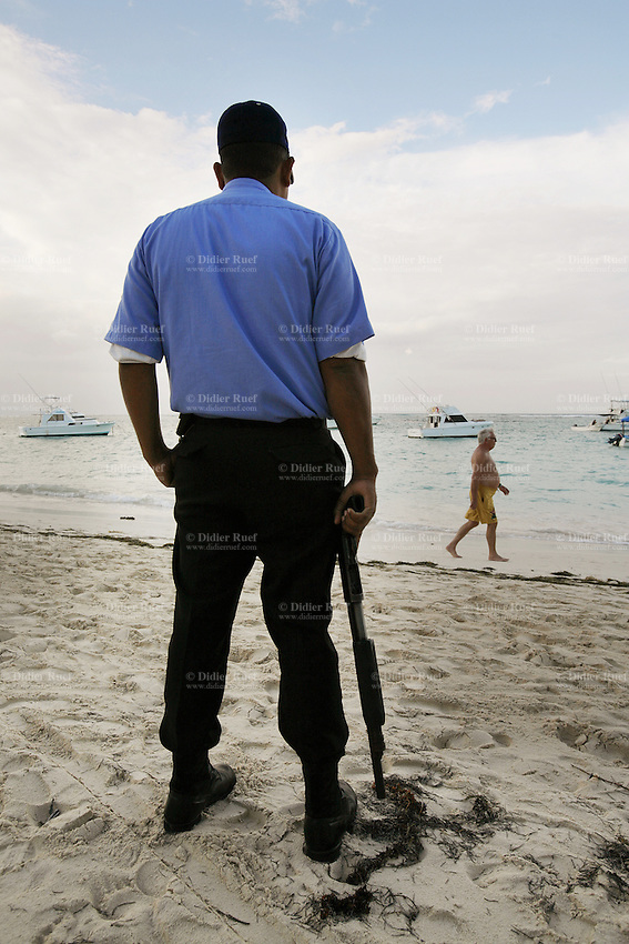 Dominican Republic. La Altagracia Province. Coastal resort of Punta Cana. Playa Bavaro. El Cortecito. A private security man, holding a rifle in his hand, looks after the safety of the tourists. Punta Cana is well-known for its beaches where meet whites sands and warm turquoise water from the Atlantic Ocean. © 2006 Didier Ruef