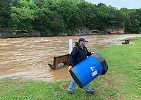 T.J. Howerton, assistant parks director for the city of West Fork, moves trash barrels and other city property Tuesday, June 1, 2021, away from the banks of the rain-swollen West Fork of the White River at Riverside Park in West Fork. Rain is expected to continue throughout Northwest Arkansas into today. Visit nwaonline.com/210602Daily/ for today's photo gallery.<br /> (NWA Democrat-Gazette/Andy Shupe)