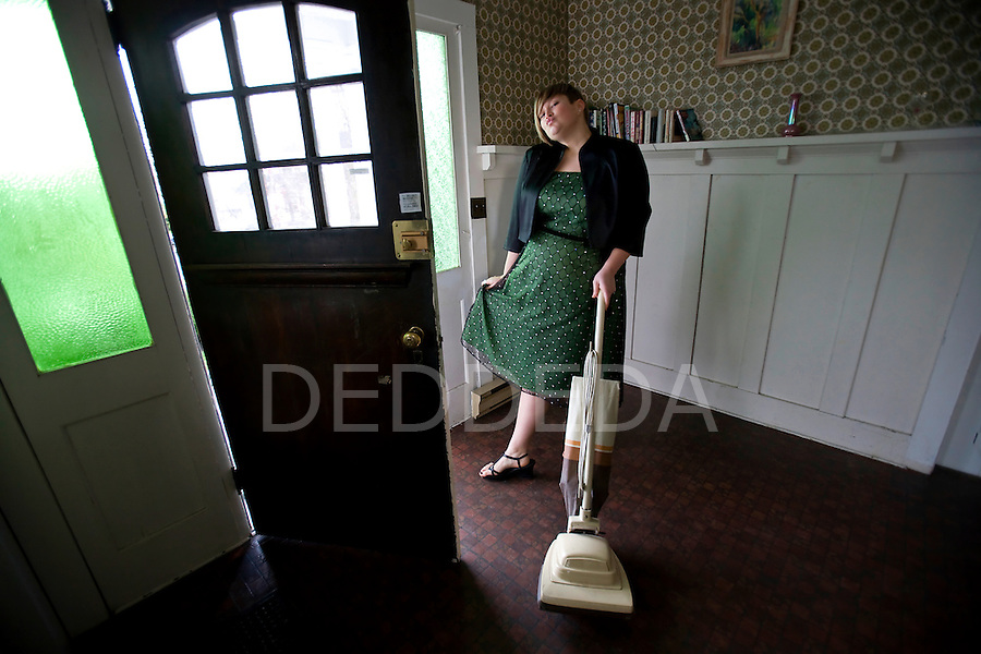 A blond woman wearing a green dress uses a retro vacuum in an old character house.