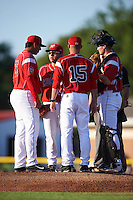 Batavia Muckdogs pitching coach Chad Rhoades (15) talks with starting pitcher Javier Garcia (36) through first baseman Eric Gutierrez (43) who translates as catcher Alex Jones (55) and umpire Lorenz Evans listen in during a game against the Aberdeen Ironbirds on July 14, 2016 at Dwyer Stadium in Batavia, New York.  Aberdeen defeated Batavia 8-2. (Mike Janes/Four Seam Images)