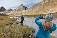 Hiker takes a picture in the Arrigetch Peeks, Arrigetch creek, Gates of the Arctic National Park, Alaska.