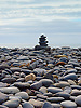 A cairn is a man-made pile (or stack) of stones. The word cairn comes from the Scottish Gaelic: càrn. <br /> <br /> Cairns are used as trail markers in many parts of the world, in uplands, on moorland, on mountaintops, near waterways and on sea cliffs, as well as in barren deserts and tundra. They vary in size from small stone markers to entire artificial hills, and in complexity from loose conical rock piles to delicately balanced sculptures and elaborate feats of megalithic engineering.<br /> <br /> A Cairn built from flat pebbles on the West Beach at Aberystwyth.<br /> <br /> Stock Photo by Paddy Bergin.