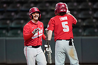 Brent Todys (12) of the Ohio State Buckeyes, left, is greeted by Nick Erwin after scoring an insurance run in the 13th inning of a 6-3 win over the Illinois Fighting Illini on Friday, March 5, 2021, at Fluor Field at the West End in Greenville, South Carolina. (Tom Priddy/Four Seam Images)