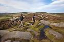 Walkers on Over Owler Tor. Peak District National Park, South Yorkshire, UK. September. Model Released.