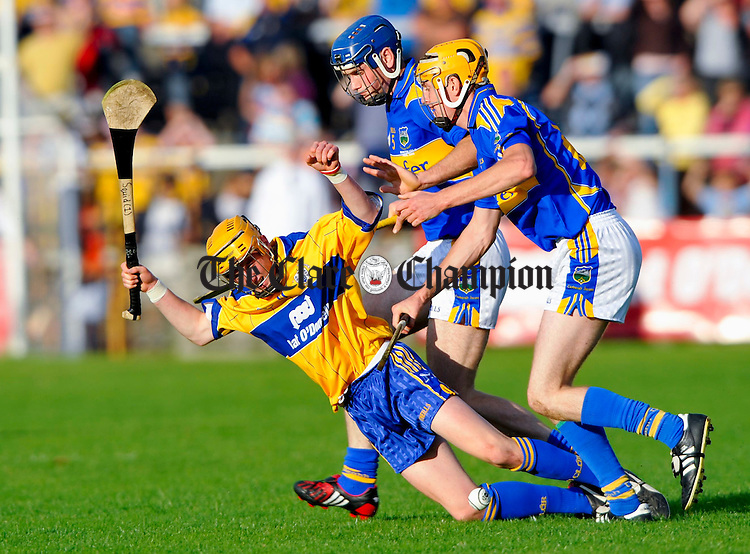 Clare's Ger Arthur hits the deck under pressure from Tipperary's Kevin Lannigan and Seamus Callinan during the Munster U-21 final at Cusack Park. Photograph by John Kelly.