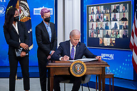 US President Joe Biden, with Margaret Purce (L), Megan Rapinoe (C) and other members of the U.S. Soccer Women's National Team, signs a proclamation during an event to mark Equal Pay Day in the State Dining Room of the White House in Washington, DC, USA, 24 March 2021. Equal Pay Day marks the extra time it takes an average woman in the United States to earn the same pay that their male counterparts made the previous calendar year.<br /> CAP/MPI/RS<br /> ©RS/MPI/Capital Pictures