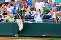 August 13, 2009: First baseman Ben Lasater (23) of the Greensboro Grasshoppers robs a fan of a souvenir as he grabs a foul ball during a game at Fluor Field at the West End in Greenville, S.C. Photo by: Tom Priddy/Four Seam Images