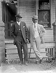 """GEORGE W. BUTCHER AND FRIEND<br /> The address on the house behind these well-appointed gentlemen is """"2001,"""" corresponding with the home of George and Fronia Butcher at 2001 U Street in Lincoln. Butcher (thought to be the taller man) was born in Philadelphia in 1874, died at the V. A. Hospital in Lincoln in 1958. He worked for Chicago & Rock Island R.R. as a porter and for Burlington R.R. as a laborer in the Havelock Shops and later as an """"ashman"""" at the municipal power plant. Fronia Butcher was even more long-lived, reaching 100 years of age (1879-1979). His dapper companion in this portrait remains unidentified.<br /> <br /> Photographs taken on black and white glass negatives by African American photographer(s) John Johnson and Earl McWilliams from 1910 to 1925 in Lincoln, Nebraska. Douglas Keister has 280 5x7 glass negatives taken by these photographers. Larger scans available on request."""