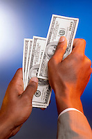 Hands holding $100 dollar bills.