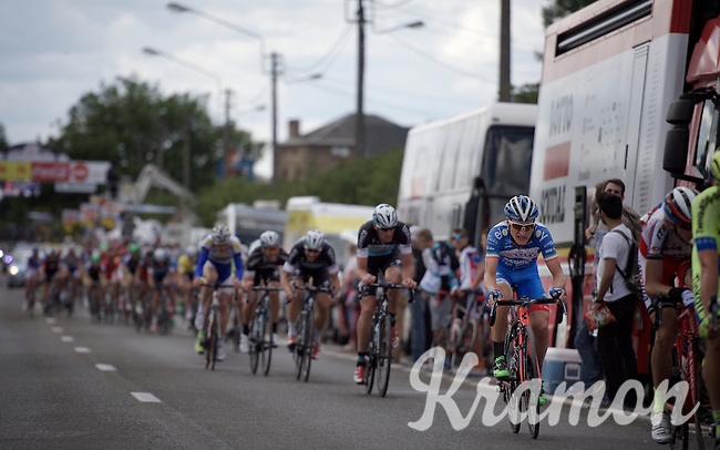 peloton charging through the finish area (in front of the team buses) 1 last time (in the final local lap)<br /> <br /> Tour de Wallonie 2015<br /> stage 5: Chimay - Thuin (167km)