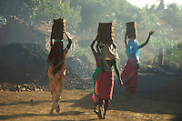 These women carry some 12 bricks each on a small construction site on the road from Mumbai to Goa about 3 hours from Mumbai,India, the brick furnace is near by hence the dust and smoke
